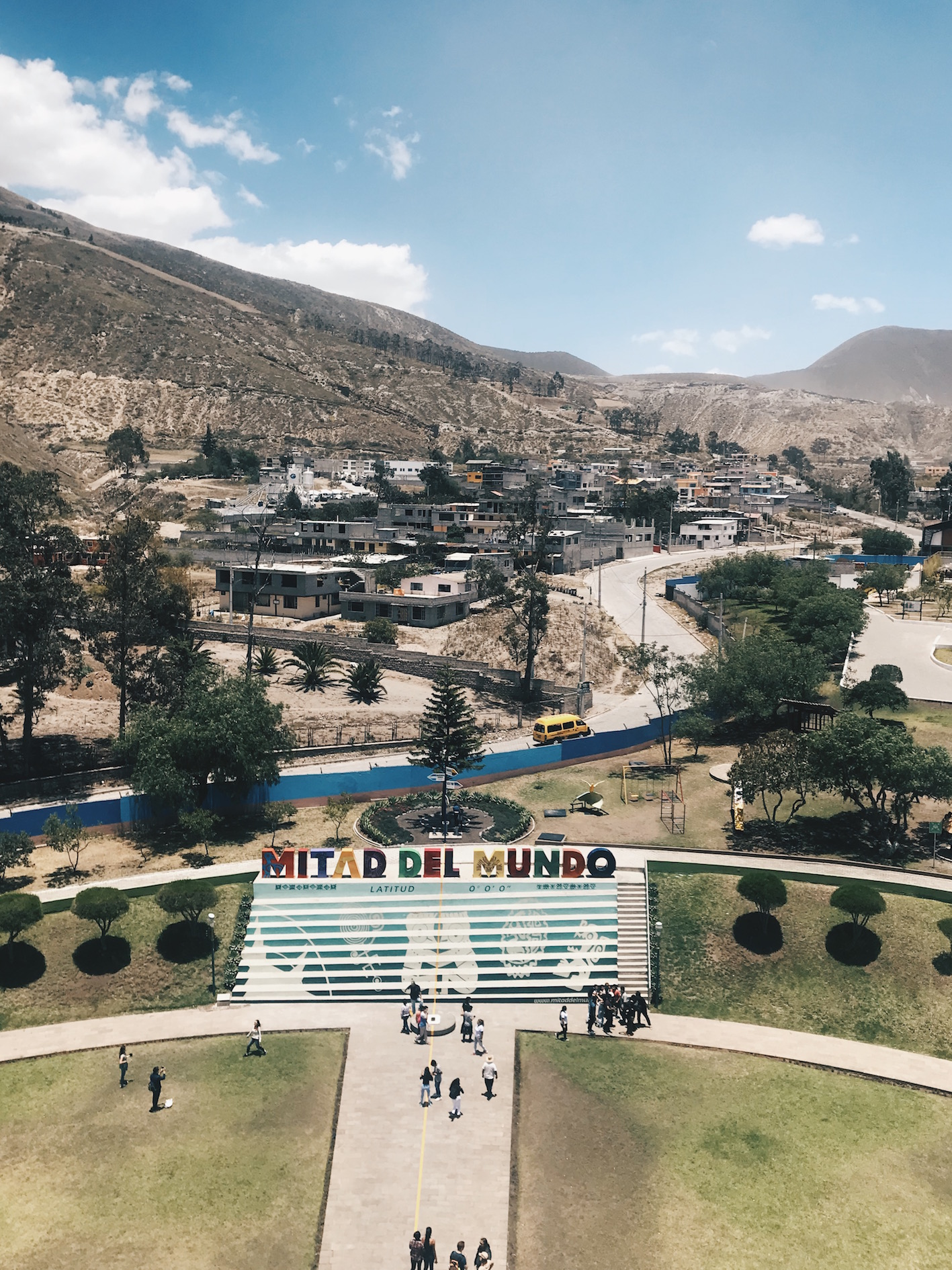long shot of the town and hills view with colourful sign saying 'mitar del mundo'