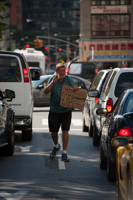 Homeless man with cardboard sign walks through cars in new york street