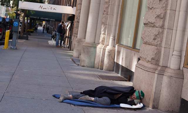 homeless man with no shoes on sleeps in open street in new york