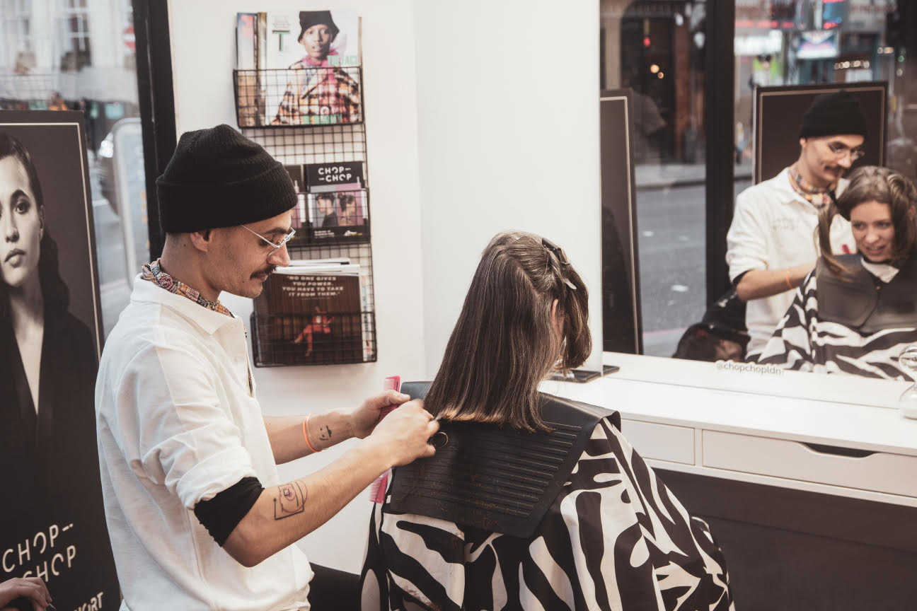 a man cutting a womans hair with a mirror in front