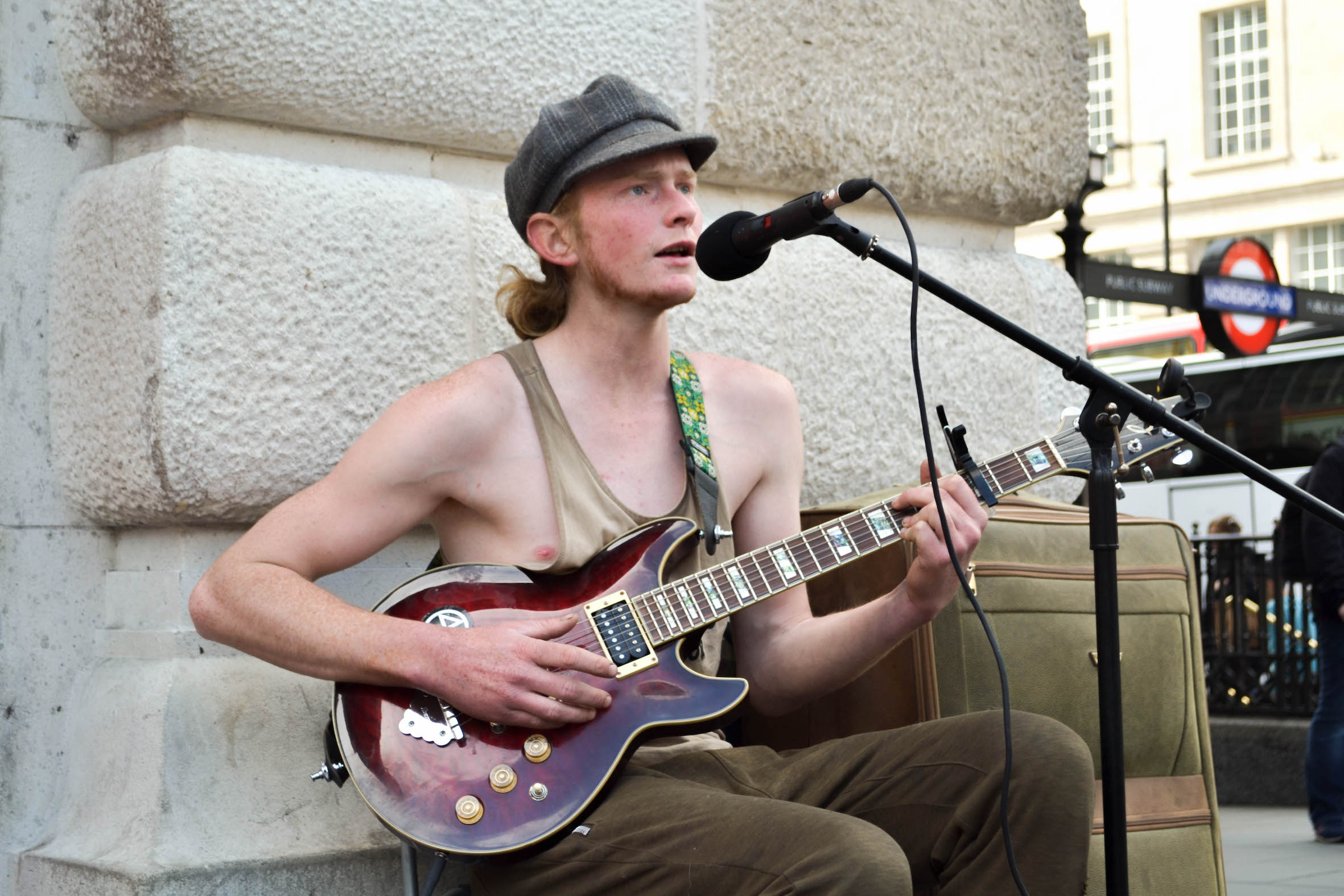 man in string vest playing guitar