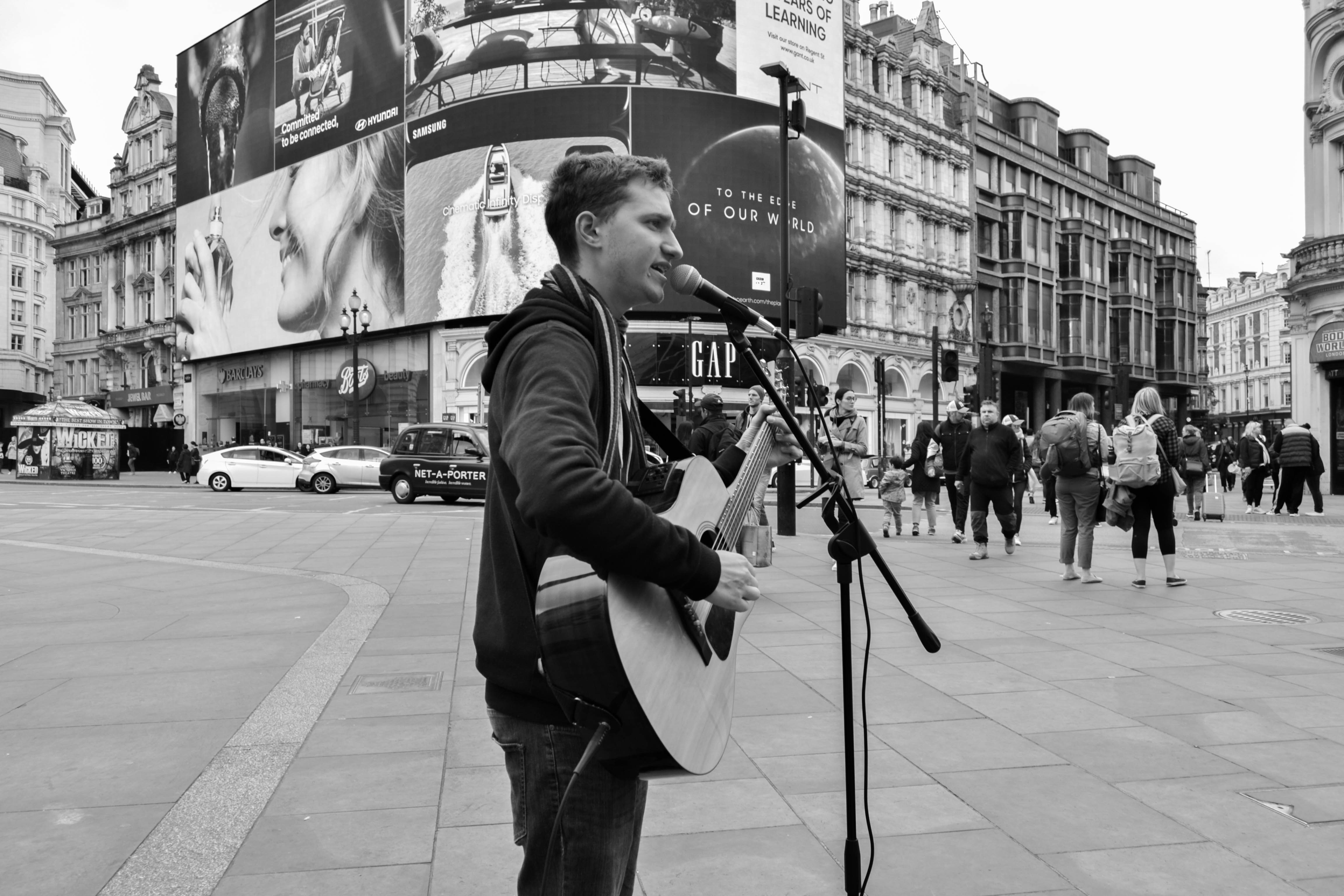 black and white picture of man busking in Piccadilly circus