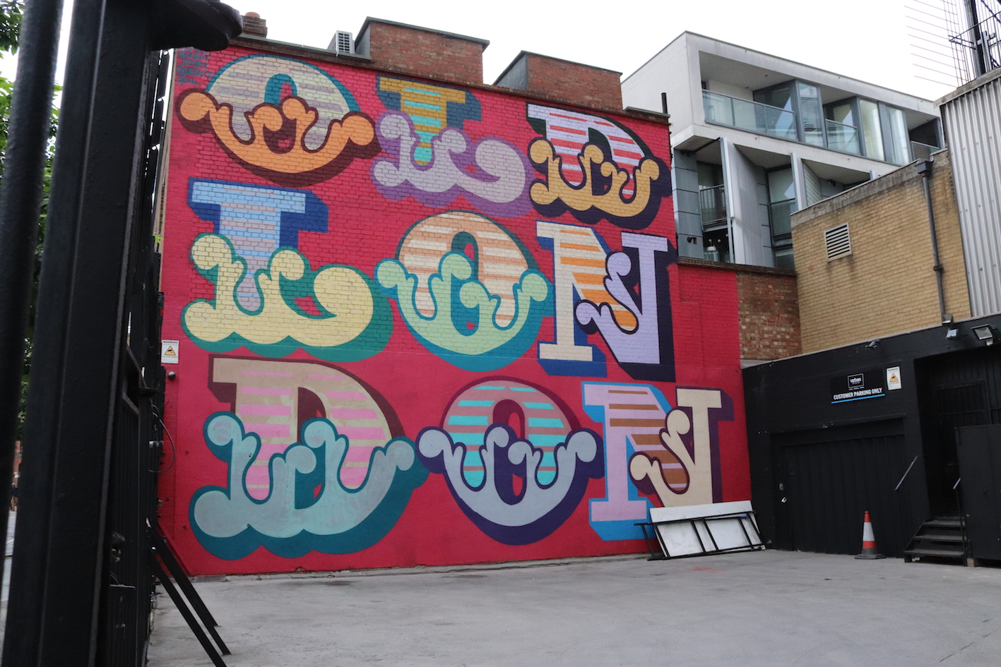 red wall with repeated london graffiti