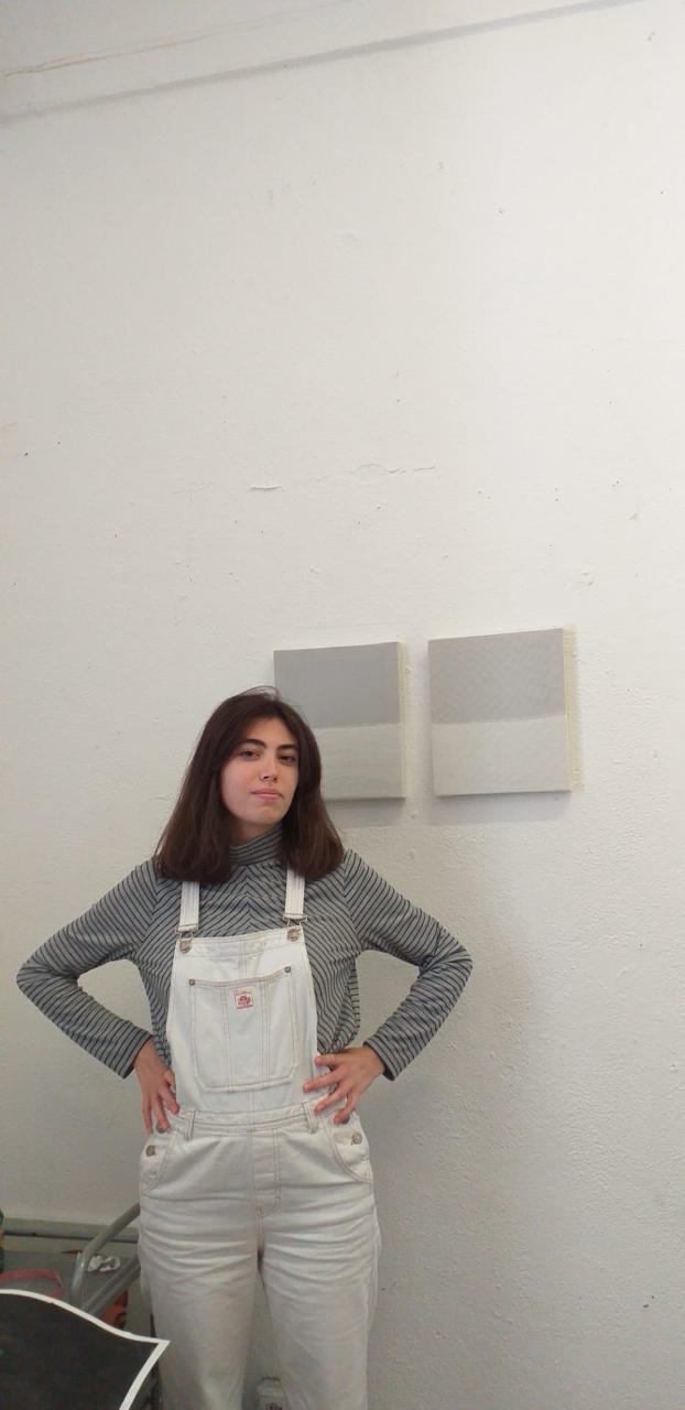 Girl stood up in front of her art work
