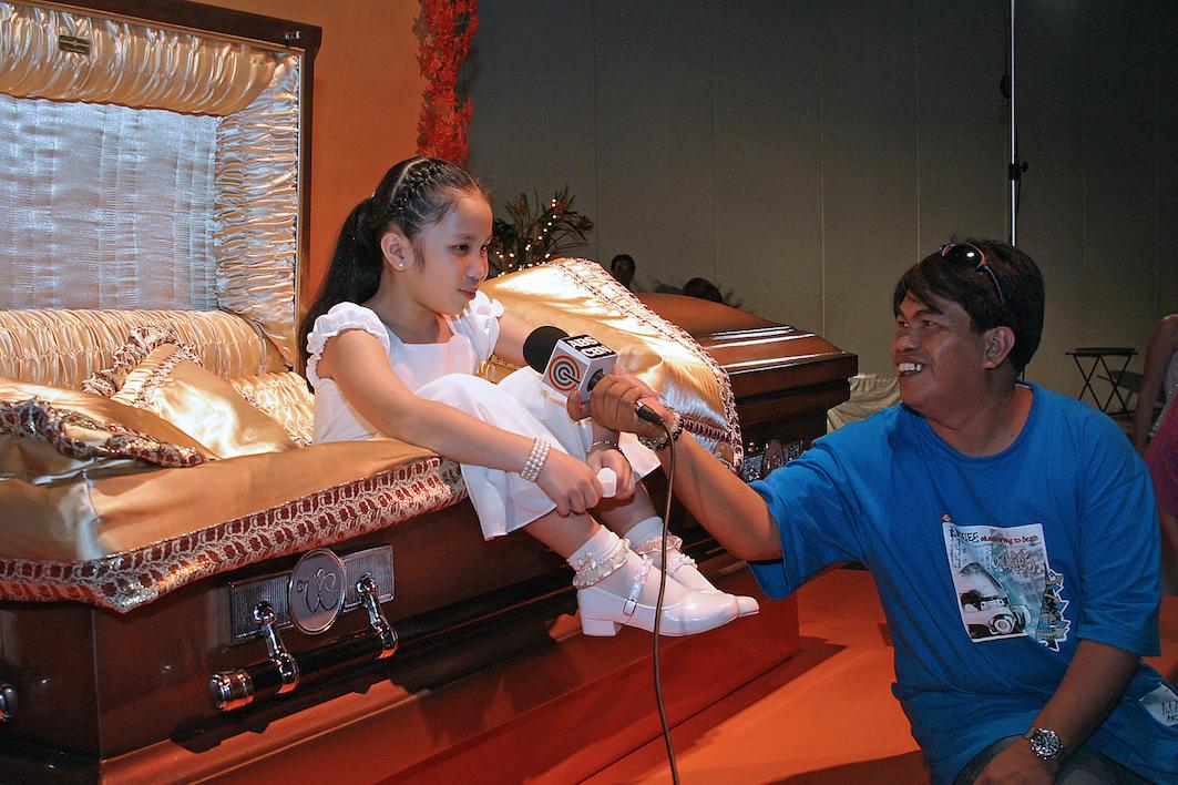 girl in pink casket being interviewed