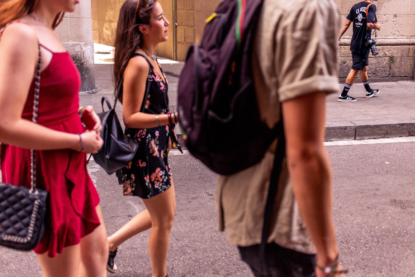 a man and two girls walking down the streeti in barcelona
