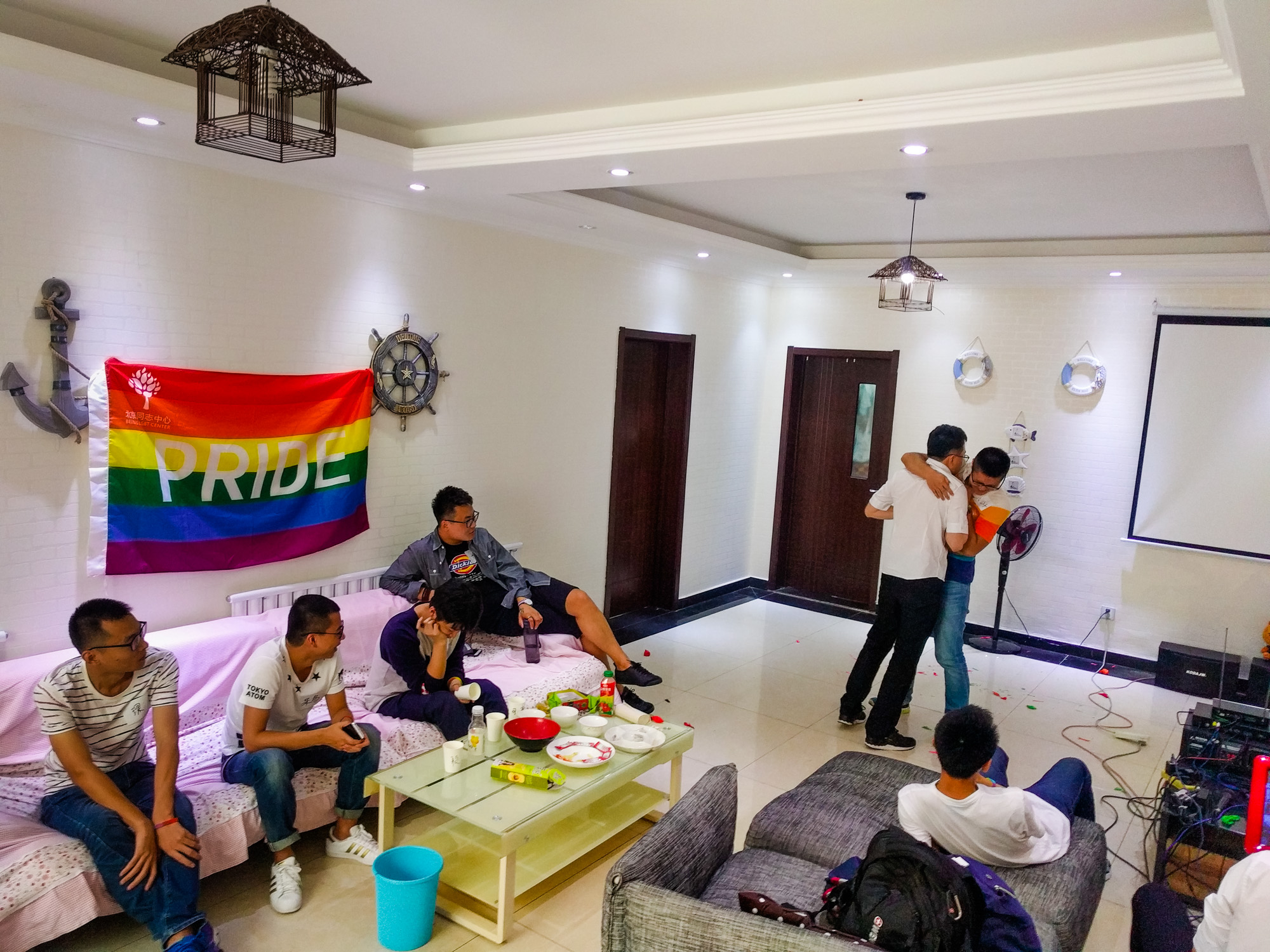 chinese men celebrating pride woth big rainbow flag in their room