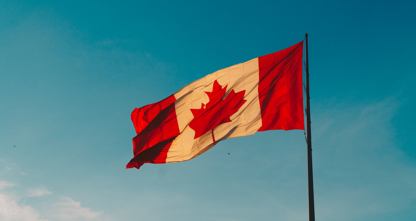 canadian flag with blue sky