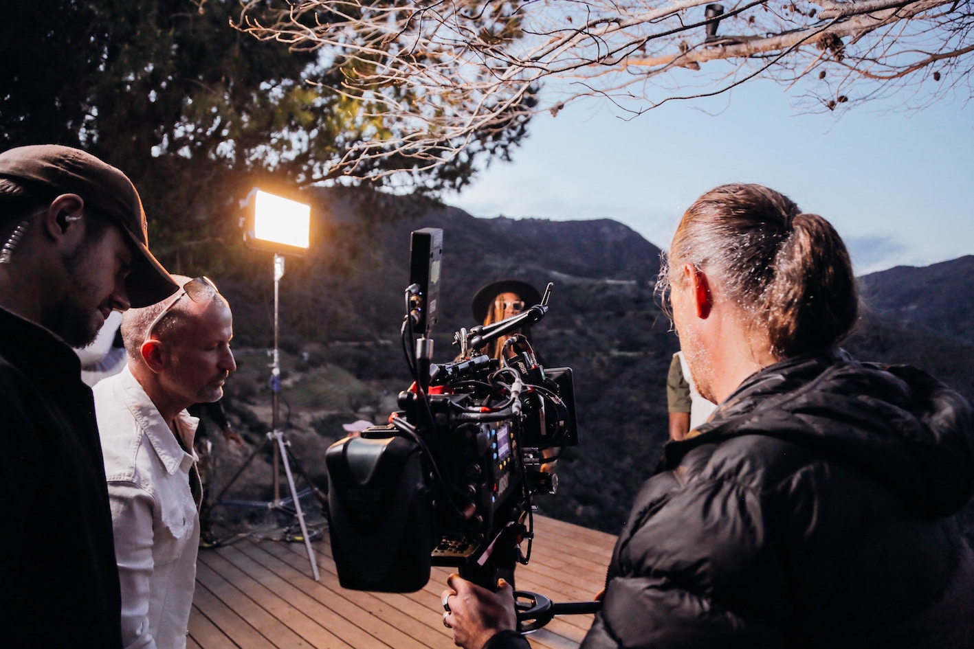 film crew and director behind camera in countryside scene