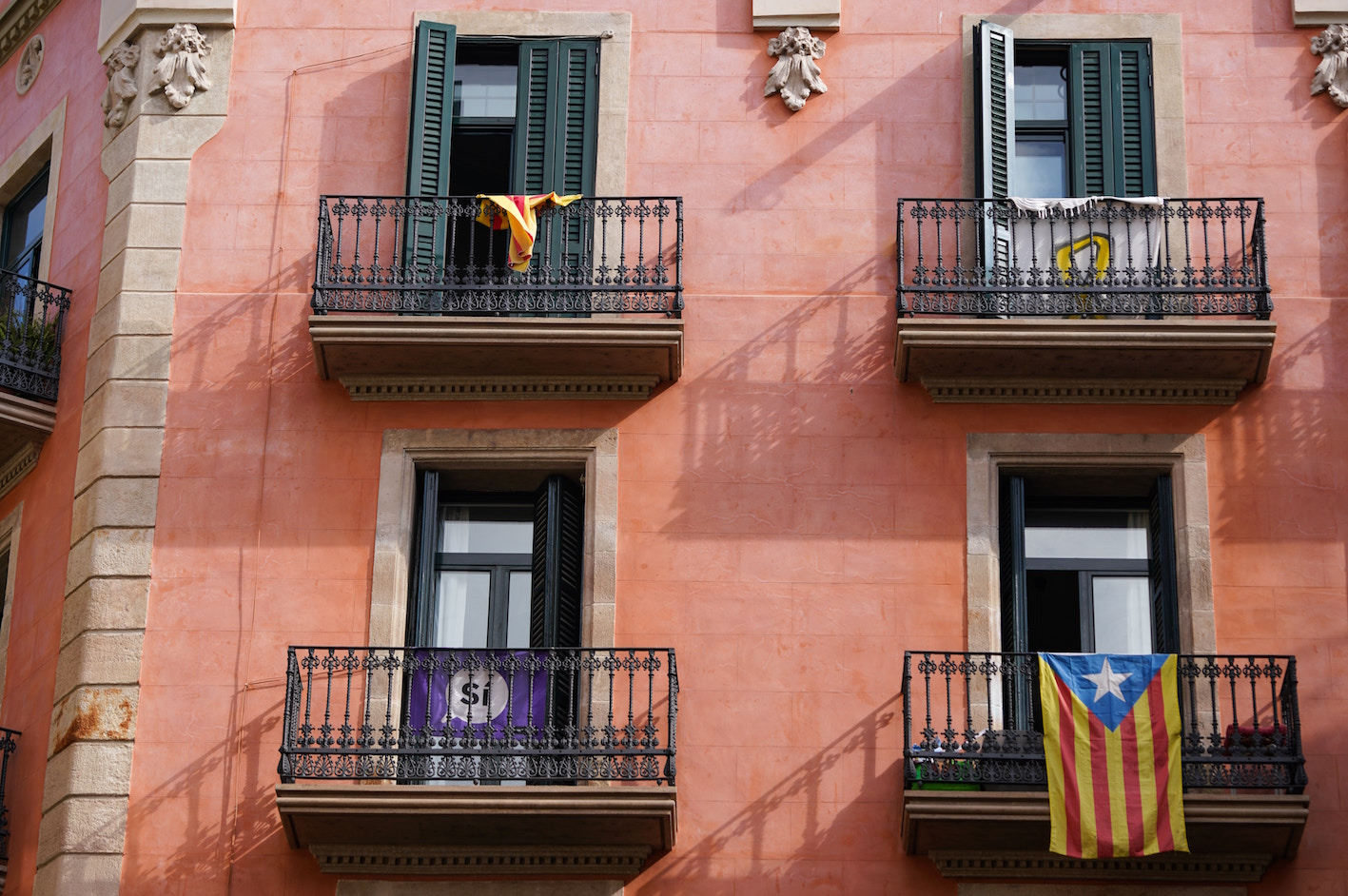 A pink building in barcelona with spanish flag hanging down
