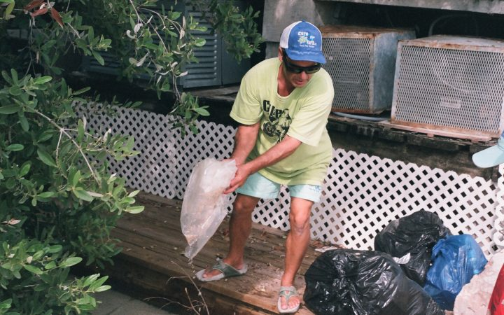 David Weinberg is picking up plastics that he has found on a pier in George Town, Bahamas