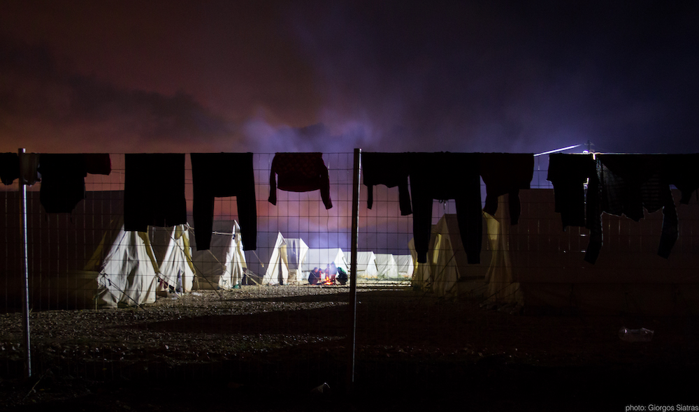 Image from the outside of a refugee camp at night, showing clothes hanging on a washing line and tents in the distance
