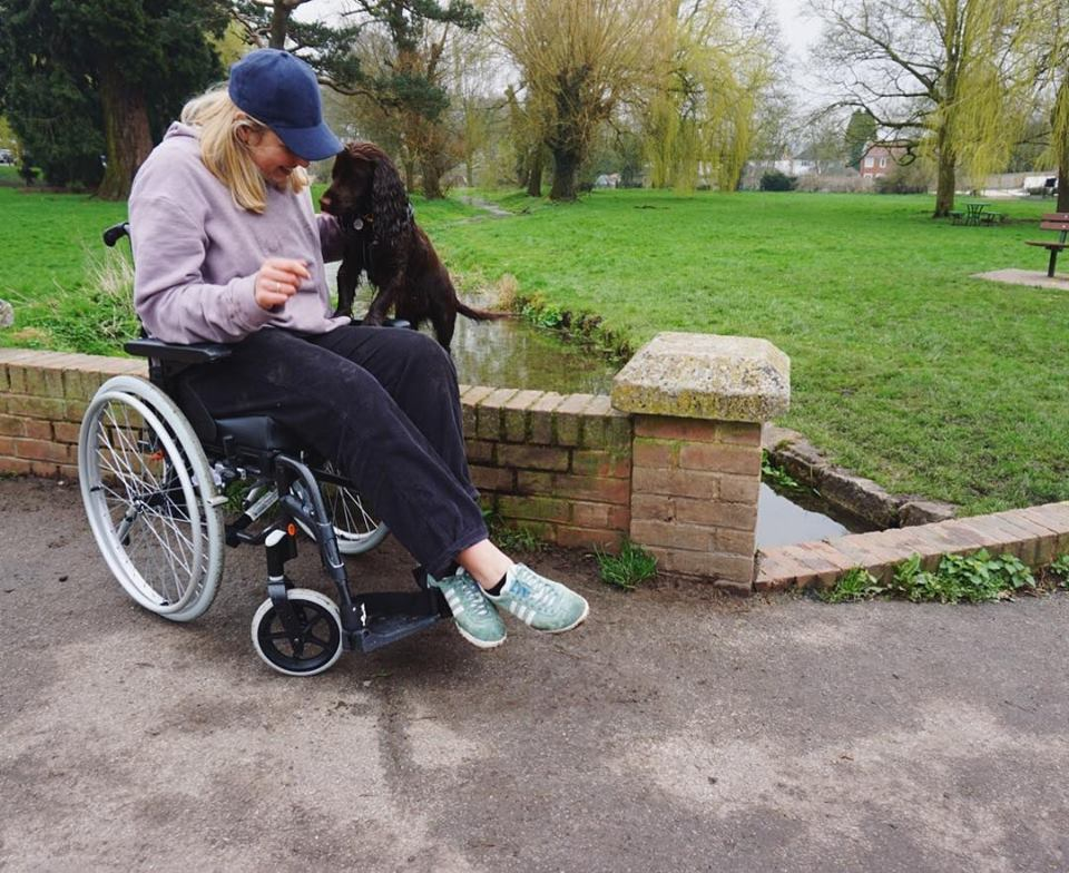 ME sufferer Ellie Bunce playing with her dog while sitting on a wheelchair