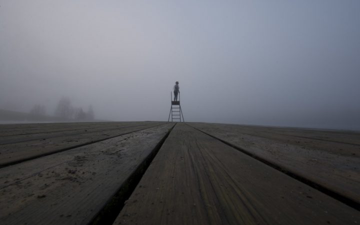 A person standing on a ladder surrounded by mist.