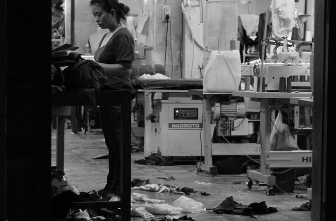 An Asian female factory worker, completing textile tasks into the night on her own.