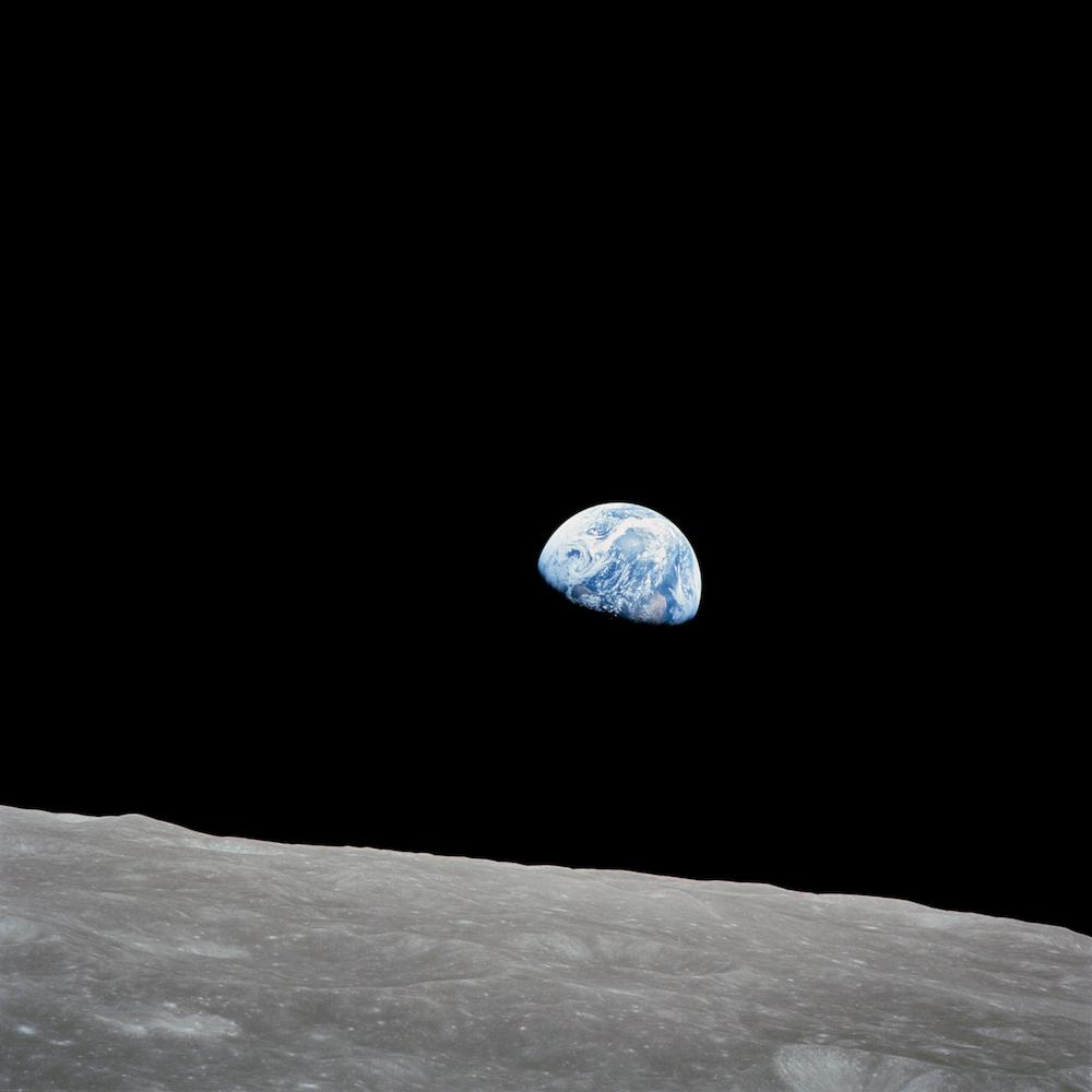 A picture of Earth rising over the moons horizon.