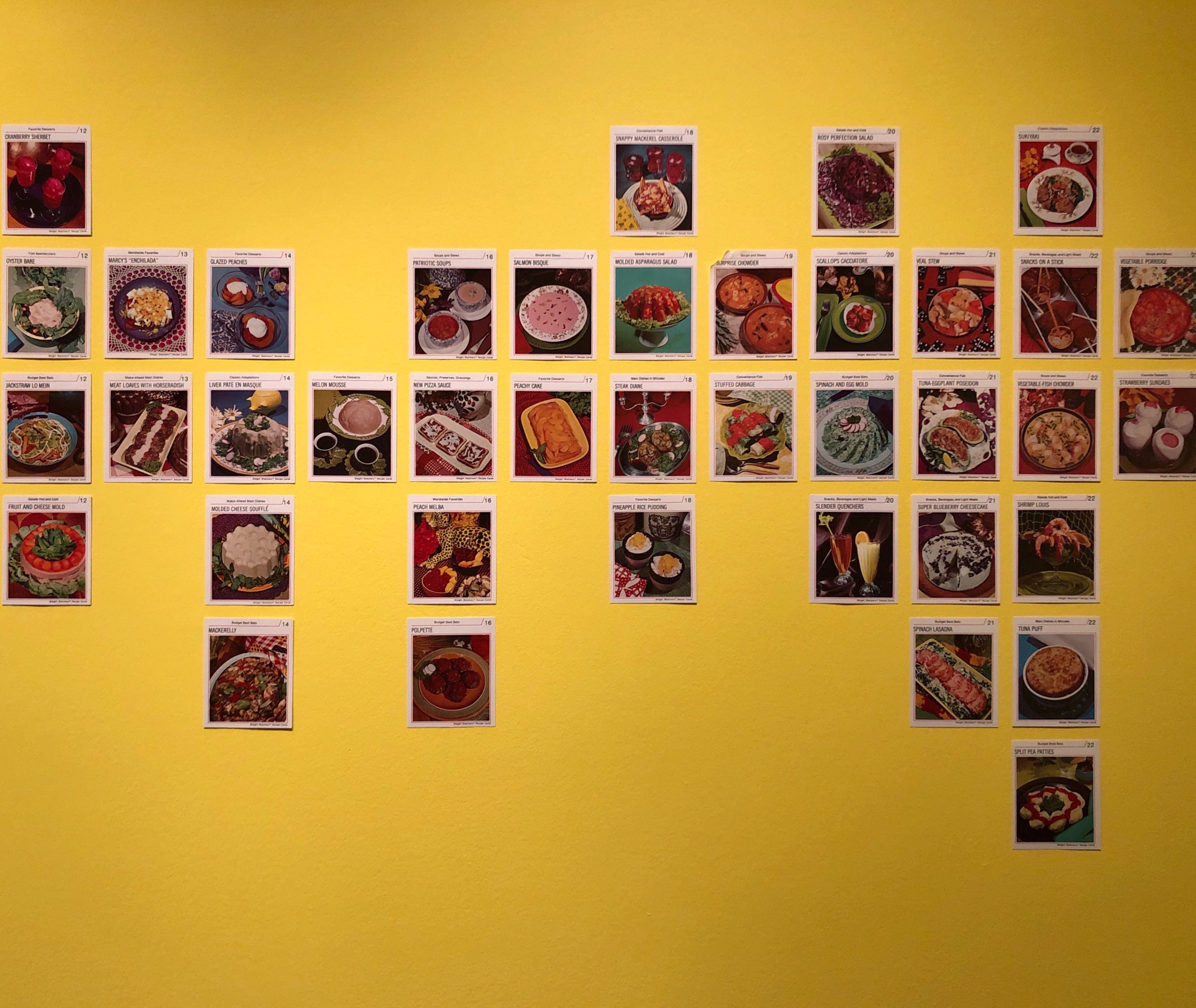 A wall-mounted assortment of recipe cards distributed by WeightWatchers in the 1970s.