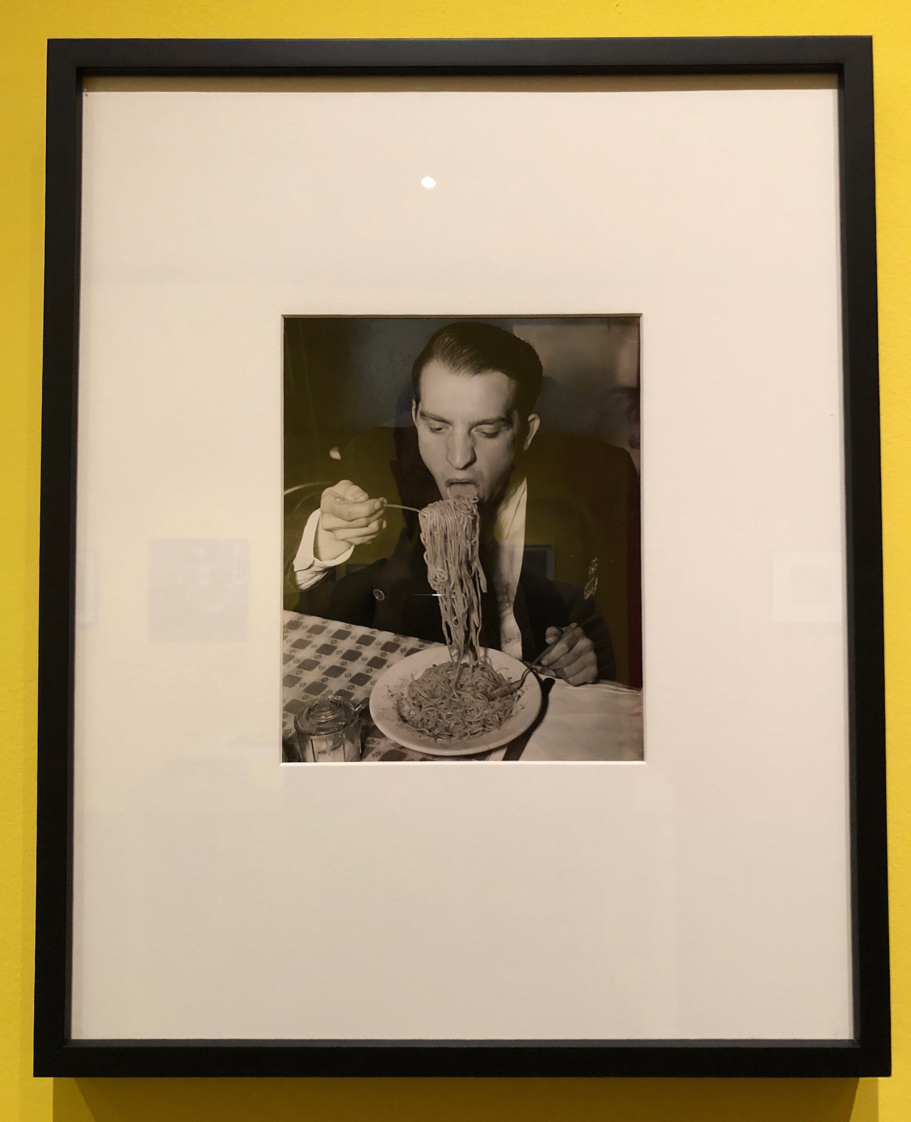 In a 1940 photograph by Weegee, Phillip J. Stazzone enjoys a large mouthful of spaghetti .