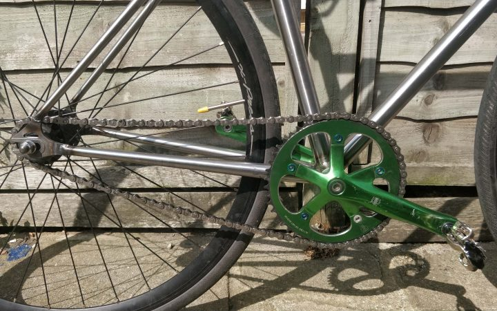 A picture of a fixed gear drive chain set up, there is one cog at the front connected to he crank arms and a smaller one at the back attached to the wheel.