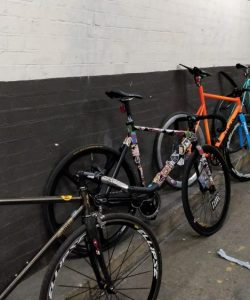 Fixed ear bikes of numerous different styles lean up against a wall at a meet up