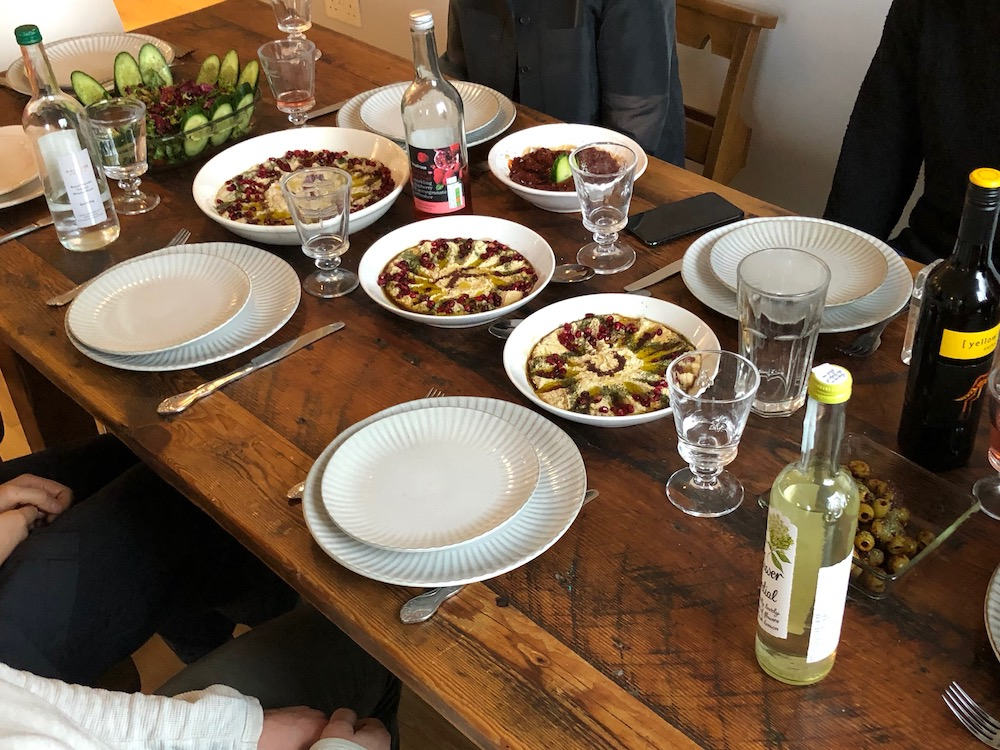 Photo of the table at the supper club, which is set for the guests to begin eating and there is three bowls of hummus and babaganoush
