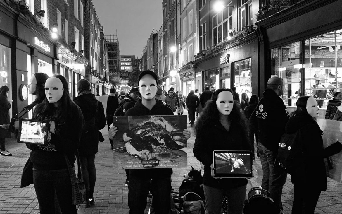 White masked animal rights activists protesting outside fashion retailers in London.