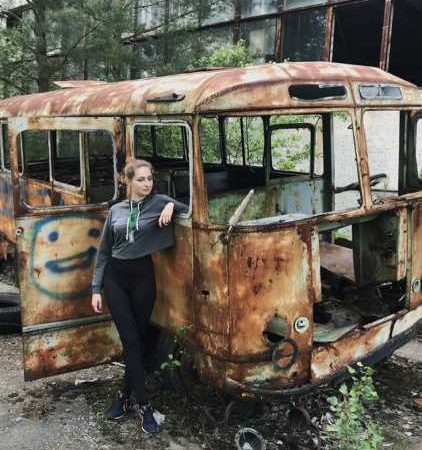Influencer leaning against Chernobyl's ruins
