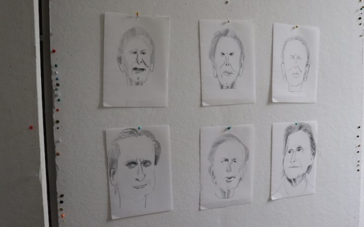sketches of 6 faces pinned on his studio wall