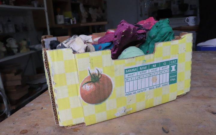 a fruitbox full of different brightly coloured plasticine