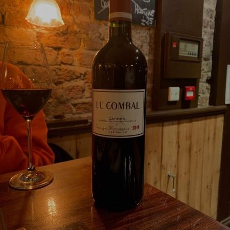 """close up of the """"Le Combal"""" wine bottle and a glass"""