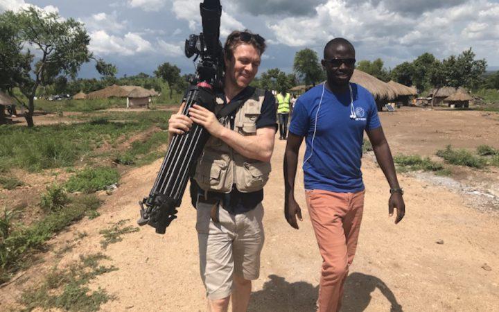 Two men walking towards camera. One holds tripod.