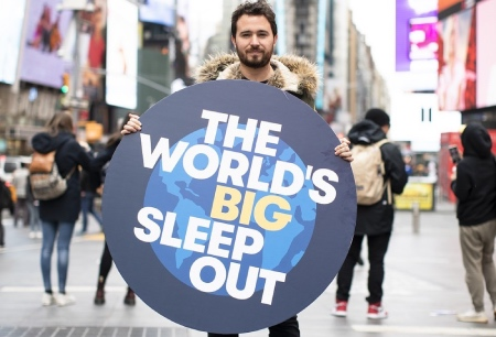 The World's Big Sleep Out founder Josh Littlejohn stands in Times Square with a large round placard for the campaign.