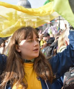 Lauren holding a yellow scarf over her head at the protest