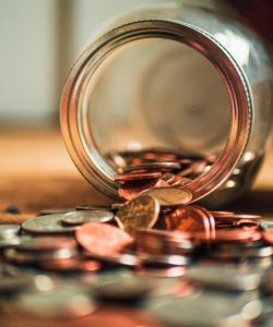Close up of a jar of coins split over a table.