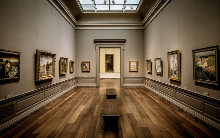 An image of an art gallery. Paintings line the walls, there are no people present.