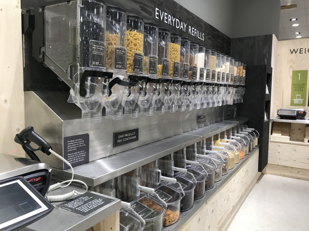 Rows of dry food dispensers from Waitrose's Unpacked scheme featuring pasta, lentils, rice, and cereals.