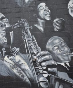 Black and white mural of people playing instruments and singing