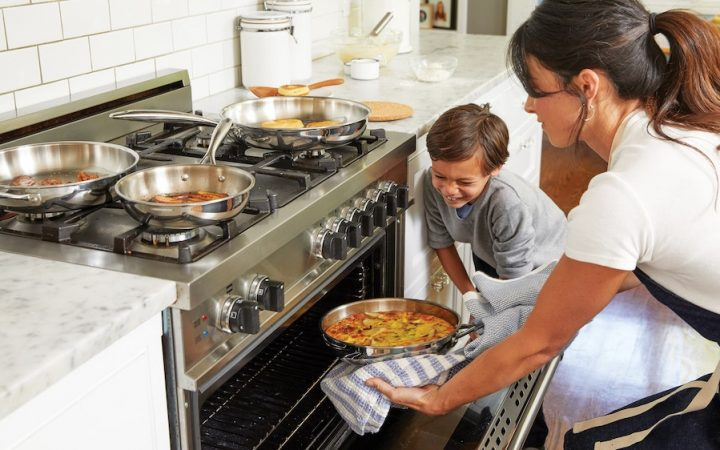 Mother pulls out food dish from the oven, her son watching her closely.