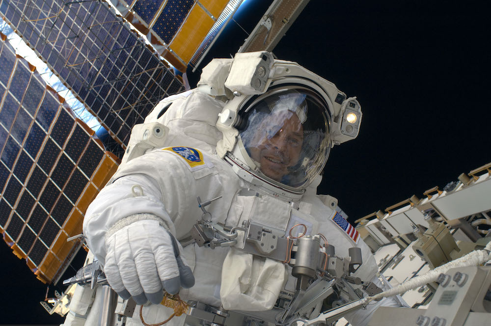 An astronaut is seen floating in space next to the international space station.