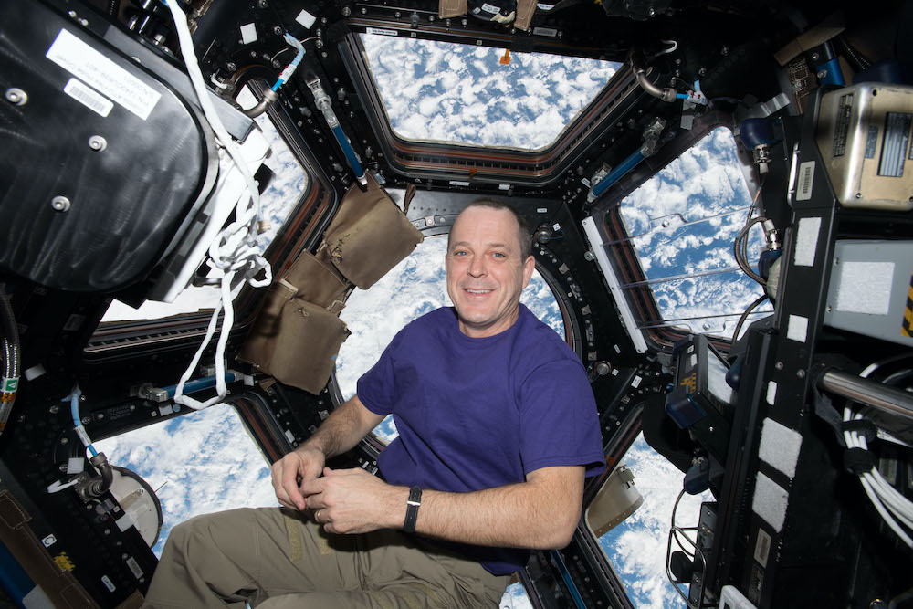 An astronaut floats inside the international space station with a view of earth behind him in windows.