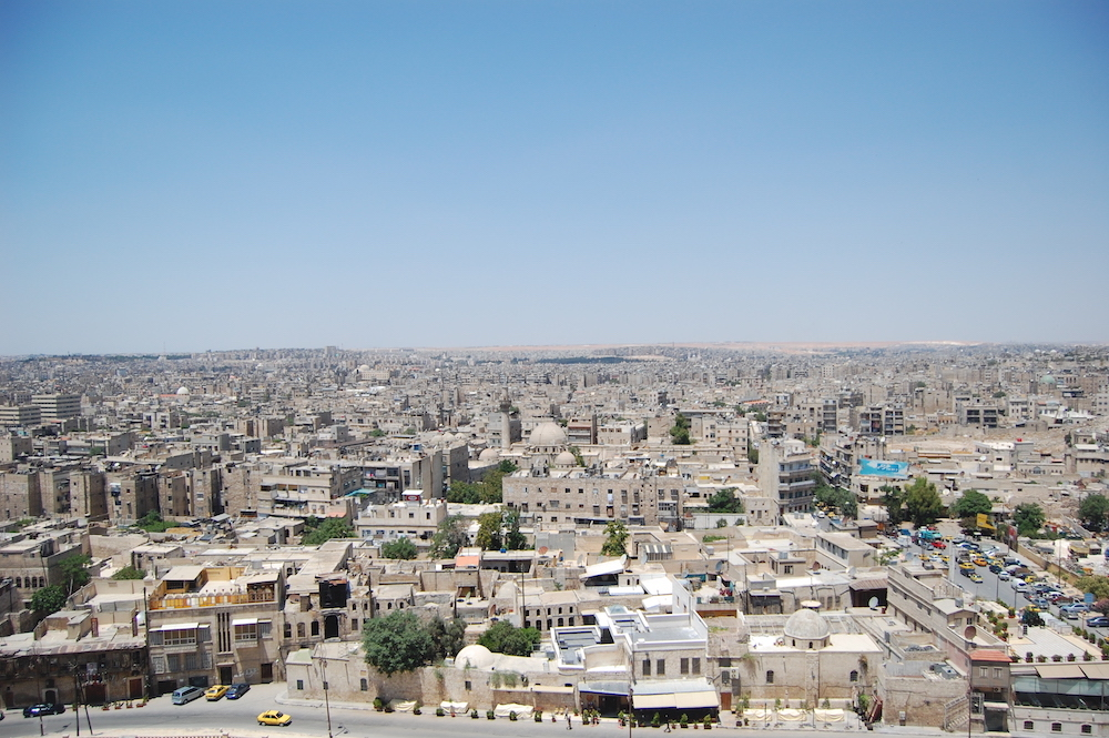 view over the city of Aleppo from the citadel, showing lots of buildings