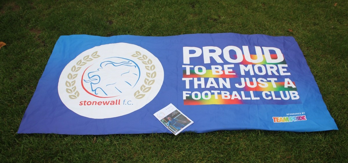 A Stonewall FC flag displayed on the grass next to the pitch. Complete with rainbow words and the Stonewall lion crest.