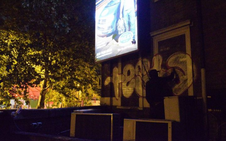 Testa painting a rooftop in South East London at night
