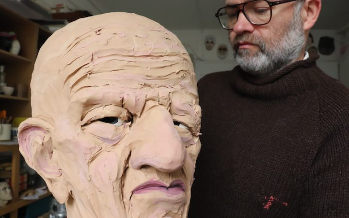 Wilfrid concerntrating on a sour looking sculpture that's straing right into the camera lens