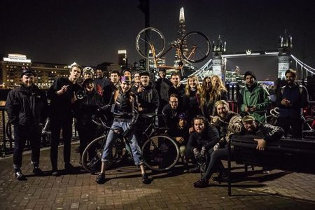 A group of cyclists posing for a picture on the bank of the river Thames.