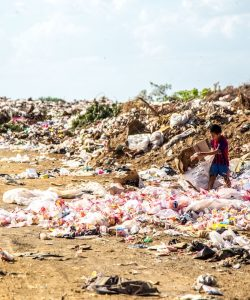 A young boy sorting through rubbish at a landfill site