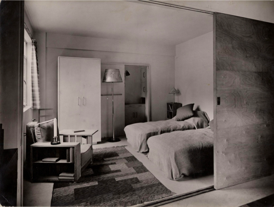 A bedroom inside one of the Isokon Flats, showcasing the use of sliding plywood door panels to save space.