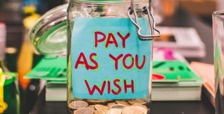 """Blue sticky note on a tip jar reading """"pay as you wish"""""""