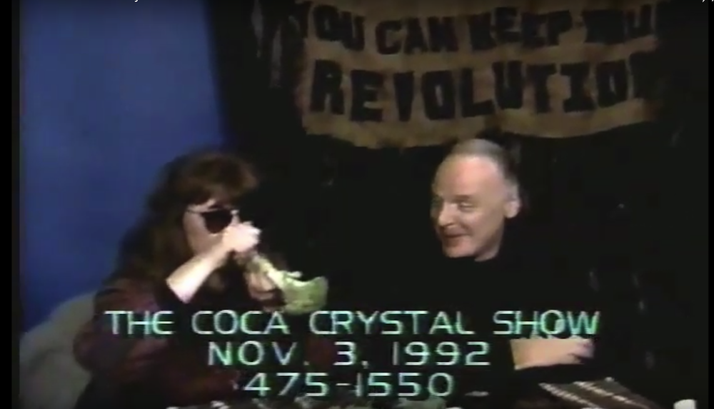 A still from The Coca Crystal Show, featuring the titular host smoking a joint through a hollowed-out broccoli.