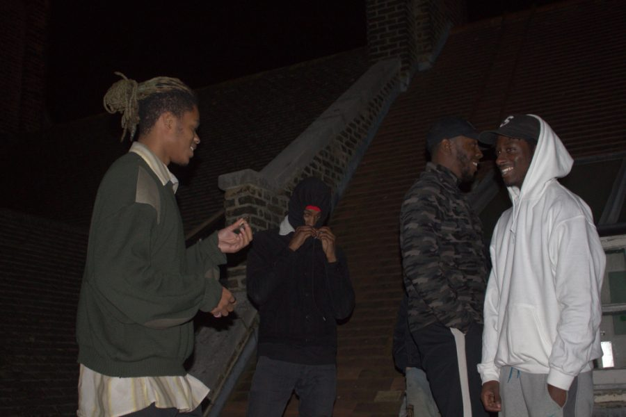 Alternative hip hop artist Danny Trash smoking a marijuana cigarette while chatting with some friends on the rooftop of his Bromley South studio.